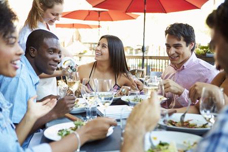 outdoor: Grupo de amigos que disfrutan comida en el restaurante al aire libre