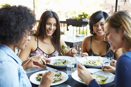 Gruppe von Freundinnen, die Mahlzeit genießen Am Außen Restaurant