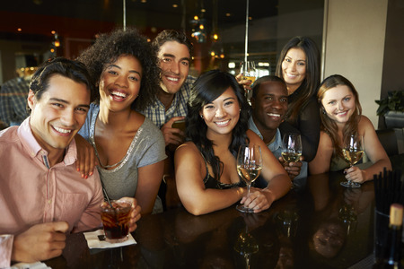 Group Of Friends Enjoying Drink At Bar Together photo