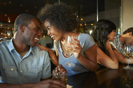 Couple Enjoying Drink At Bar With Friends 스톡 콘텐츠