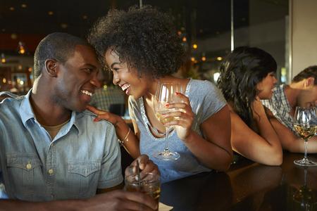 bebiendo vino: Pares que disfrutan de la bebida en el bar con los amigos