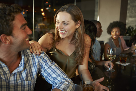 Couple Enjoying Drink At Bar With Friends photo