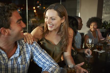Paar dat van drankje aan de bar Met vrienden Stockfoto