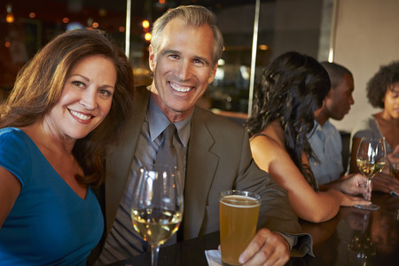 bebiendo vino: Pareja madura disfruta de la bebida en barra junto Foto de archivo
