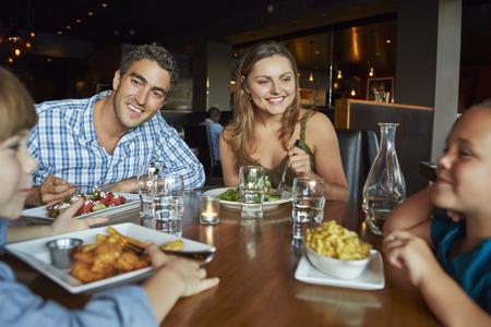 familia comiendo: Familia que disfruta de la comida en restaurante