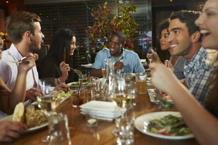 Grupo de amigos que disfrutan de la comida en restaurante Foto de archivo - 31021384
