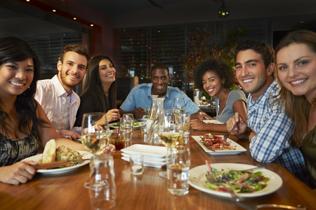people eating restaurant: Group Of Friends Enjoying Meal In Restaurant Stock Photo