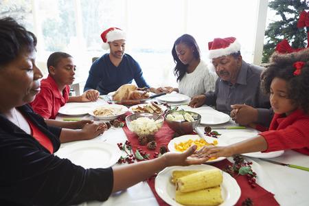 familia orando: Multi generacional ruega antes de comidas de Navidad