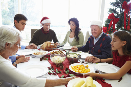 comida de navidad: Multi generacional ruega antes de comidas de Navidad