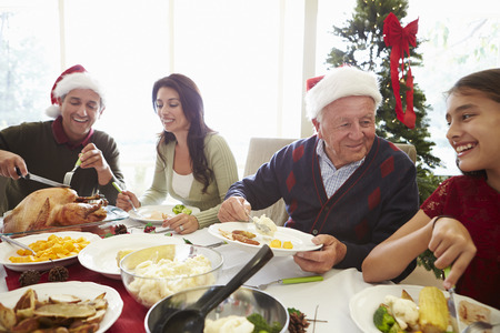 Multi Generation Familie die van Kerstmis maaltijd thuis Stockfoto