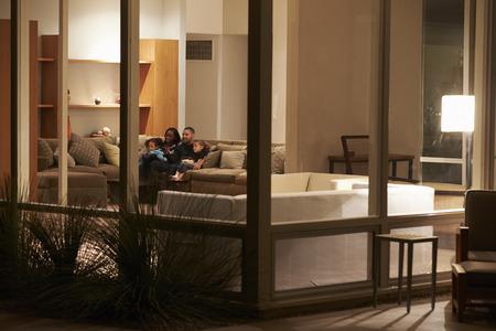 Familia viendo televisión en casa se ve desde el exterior Foto de archivo - 31021452