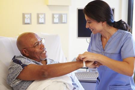 Verpleegkundige zetten Polsband Op Hogere Mannelijke patiënt in het ziekenhuis Stockfoto