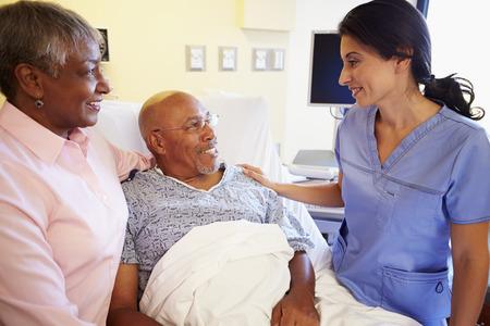 black nurse: Nurse Talking To Senior Couple In Hospital Room