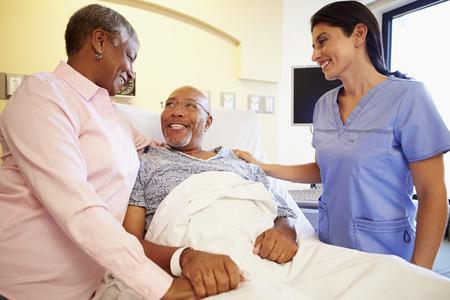 Nurse Talking To Senior Couple In Hospital Room