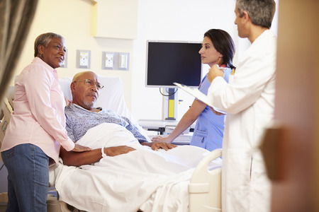 serious doctor: Medical Team Meeting With Senior Couple In Hospital Room