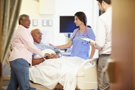 Medical Team Meeting With Senior Couple In Hospital Room photo