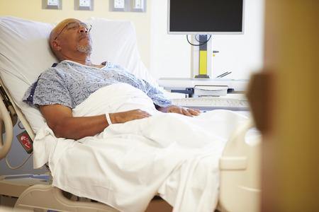 personen: Hogere Mannelijke Patiënt Rusten In Bed van het Ziekenhuis