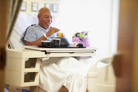 patient on bed: Senior Male Patient Enjoying Meal In Hospital Bed