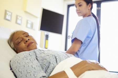 Nurse Watching Sleeping Senior Woman Patient In Hospital