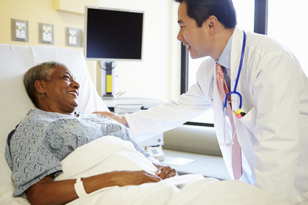 Doctor Talking To Senior Woman In Hospital Room photo