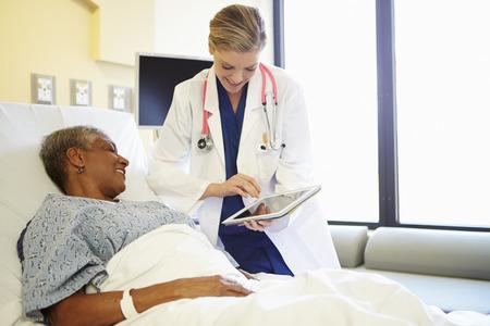 Arts met Digitale Tablet Talks To vrouw in het ziekenhuis Bed
