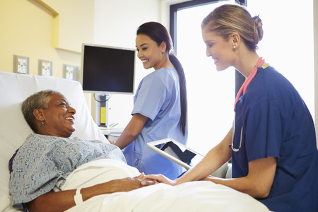 Nurse With Digital Tablet Talks To Woman In Hospital Bed Stock Photo