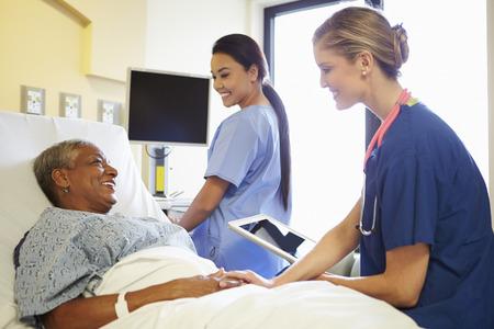 pielęgniarki: Pielęgniarka Z cyfrowym tablecie mówi do kobiety w szpitalu Bed Zdjęcie Seryjne