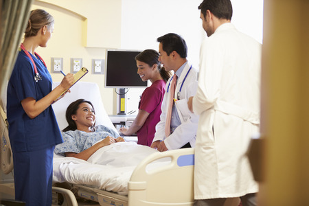doctor patient: Medical Team Meeting Around Female Patient In Hospital Room