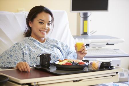 女性患者を病院のベッドで食事を楽しんで
