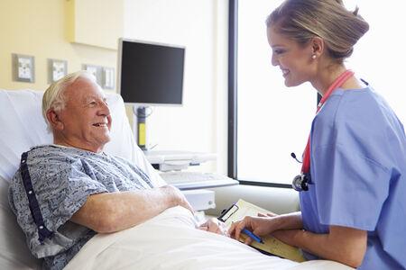Nurse Talking To Senior Male Patient In Hospital Room