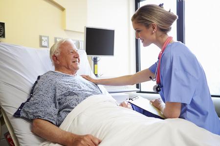 enfermera con paciente: Cuide hablar con la paciente senior masculino habitación en el hospital Foto de archivo