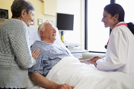 Vrouwelijke Arts Talking To Senior Couple in het ziekenhuis Kamer