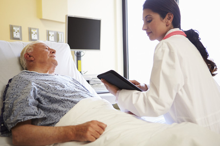 doctor computer: Doctor With Digital Tablet Talking To Patient In Hospital Stock Photo