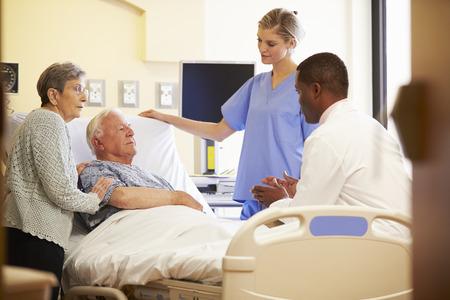 Reunión del Equipo Médico Con Pareja mayor habitación en el hospital