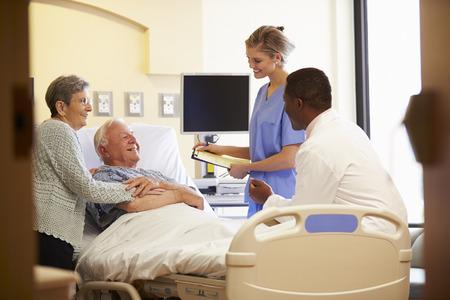病室で年配のカップルとのチーム医療会議 写真素材
