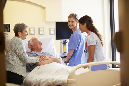 geriatric: Medical Team Meeting With Senior Couple In Hospital Room
