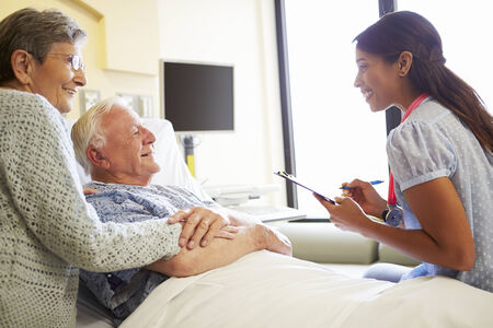 doctor writing: Female Doctor Talking To Senior Couple In Hospital Room