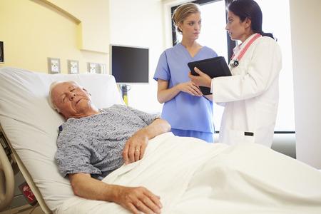 Medical Team Meeting As Senior Man Sleeps In Hospital Room photo