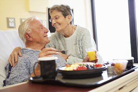 Senior Couple In Hospital Room As Male Patient Has Lunch photo