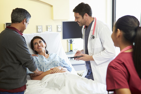 asian wife: Medical Team Meeting With Couple In Hospital Room