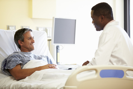 Doctor Talking To Male Patient In Hospital Room photo
