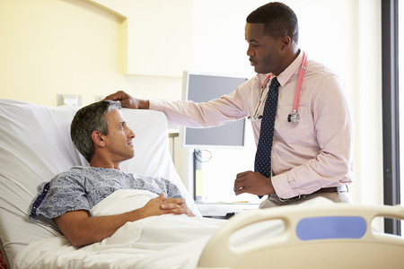 hospital room: Doctor Talking To Male Patient In Hospital Room
