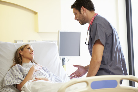 Male Nurse Talking With Female Patient In Hospital Room photo