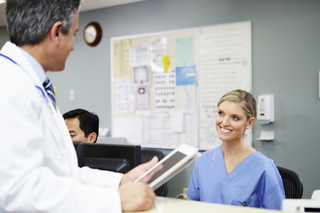 Doctor In Discussion With Nurse At Nurses Station