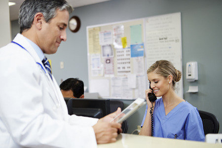 Doctor In Discussion With Nurse At Nurses Station photo