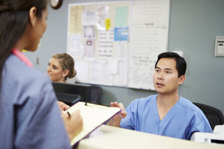 nurse station: Male And Female Nurse In Discussion At Nurses Station