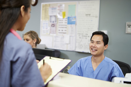 nurses station: Male And Female Nurse In Discussion At Nurses Station