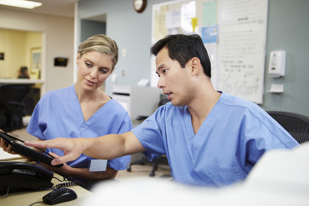 Male And Female Nurse Working At Nurses Station Stockfoto