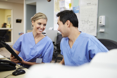 Male And Female Nurse Working At Nurses Station Stock Photo
