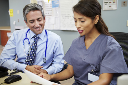 Doctor With Nurse Working At Nurses Station photo